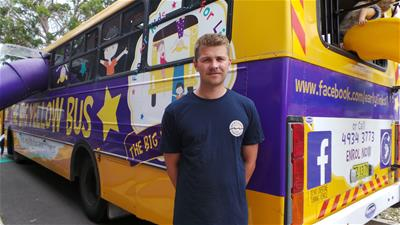 HVTC Allied Health Trainee Alex McIntosh standing in front of the Early Links Big Yellow Bus