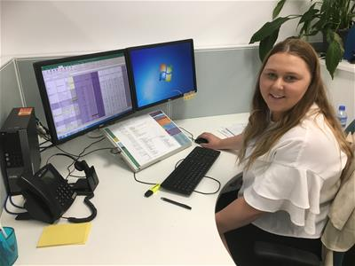 HVTC Shoalhaven trainee Paige Tate-Harrington sitting at her desk in the office