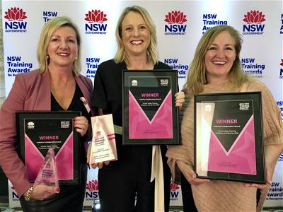 Three women with trophies celebrating  at awards event