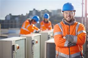 Man in orange high vis facing camera with apprentices in background working on air conditioning units