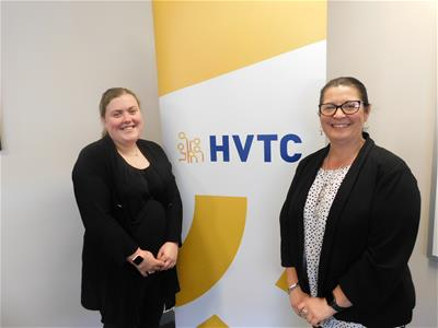 Two women standing in front of blue and yellow HVTC banner