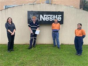 Four people standing in front of Nestle sign