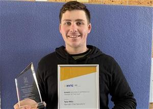 Young man with framed certificate and trophy standing in front of blue background